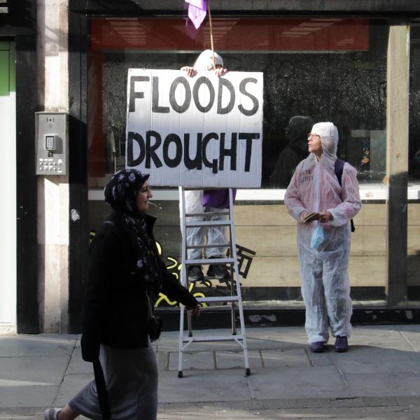 rebel on step ladder holding sign - floods drought